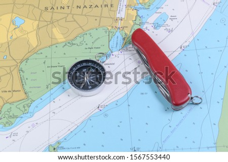 Magnetic compass and folding knife on a nautical navigational map #1567553440