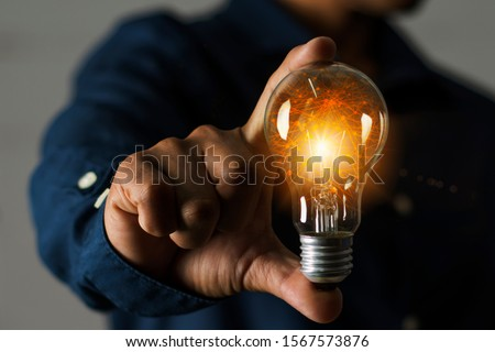 A businessman holding a light bulb in his hand demonstrates the broad vision and concept of building a business that will grow with efficiency and stability. #1567573876