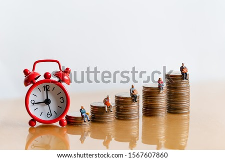 Miniature people: Red alarm clock and elderly people sitting on coins stack. Retirement planning. money saving and Investment. Time counting down for retirement and pension. #1567607860
