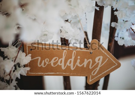 Brown and white wedding arrow sign