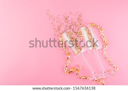 Two glasses of champagne filled with gold stars confetti on a pink pastel background surrounded by Christmas decorations.Top view. Christmas card blank. Copy space and horizontal orientation. #1567636138