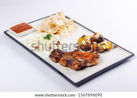grilled beef ribs and baked potato with cheese. onion circles and pita bread, red sauce on a white board. great snack dish for beer #1567696090