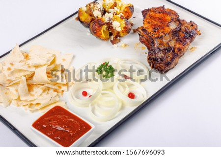 grilled beef ribs and baked potato with cheese. onion circles and pita bread, red sauce on a white board. great snack dish for beer #1567696093