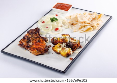 grilled beef ribs and baked potato with cheese. onion circles and pita bread, red sauce on a white board. great snack dish for beer #1567696102