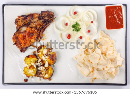 grilled beef ribs and baked potato with cheese. onion circles and pita bread, red sauce on a white board. great snack dish for beer. top view flat layout #1567696105
