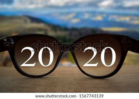 2020 white text with black eye glasses on wooden table over blur autumn landscapes. Business vision happy new year. Royalty-Free Stock Photo #1567743139