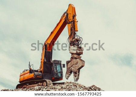 excavator destroys the building. tractor close up stands on the wreckage of the house Royalty-Free Stock Photo #1567793425