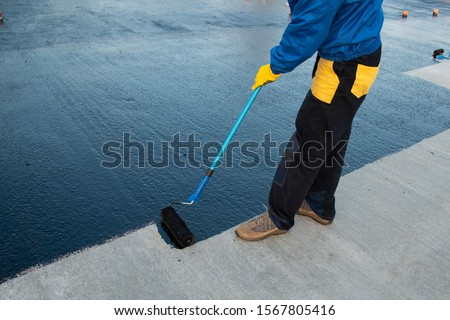 Waterproofing coating. Worker applies bitumen mastic on the foundation. Roofer cover the rooftop polymer modified bitumen waterproofing primer, with a roller brush. #1567805416