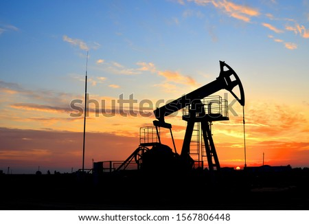 Oil drilling derricks at desert oilfield for fossil fuels output and crude oil production from the ground. Oil drill rig and pump jack background, texture. Belarus, Rechitsa region #1567806448