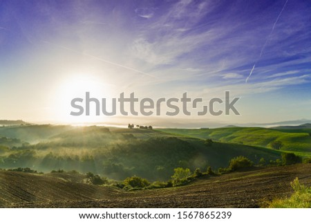 Beautiful foggy sunrise landscape in Tuscany, Italy. Tuscany landscape with morning fog with sunlight. #1567865239