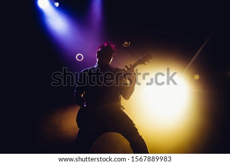 Rock band performs on stage. Guitarist plays solo. silhouette of guitar player in action on stage in front of concert crowd. #1567889983