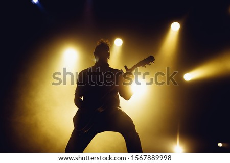 Rock band performs on stage. Guitarist plays solo. silhouette of guitar player in action on stage in front of concert crowd. #1567889998