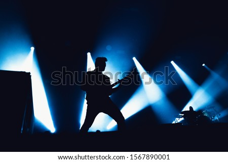 Guitarist plays solo. silhouette of guitar player in action on music stage. popular music rock band performs on stage. #1567890001