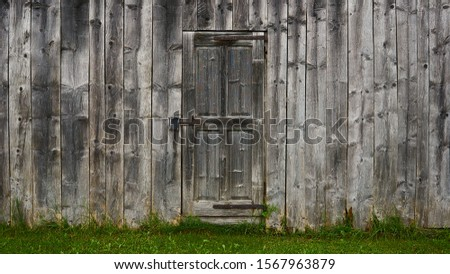 Old weathered rustic textured wooden barn wall with single door showing great patina and dark green grass contrast at bottom.                               #1567963879