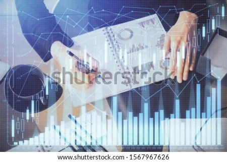 Multi exposure of hands making notes with forex chart huds. Stock market concept. #1567967626