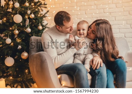 Happy family of mother, father and little baby boy celebrating new year in front of Christmas tree in decorated interior. Celebrating Christmas. #1567994230