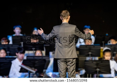 Back view of a male band conductor in formal suit conducting his concert band #1568051098