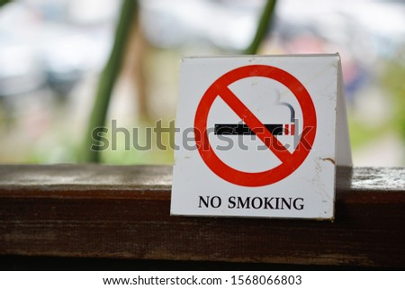 No smoking sign on the wooden floor in the garden.Square sign