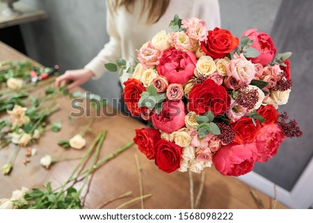 European floral shop concept. Florist woman creates red beautiful bouquet of mixed flowers. Handsome fresh bunch. Education, master class and floristry courses. Flowers delivery. Royalty-Free Stock Photo #1568098222