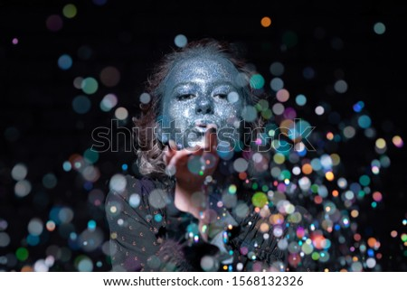 girl with a blue face in sparkles listens to photography tips from the photographer