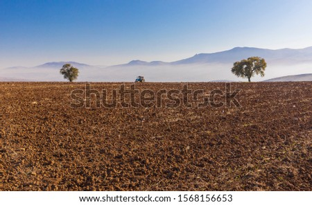 Tractor plows the earth against the backdrop of mountains and fog #1568156653