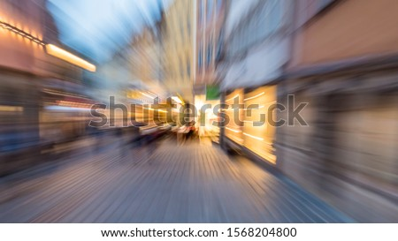 Zoom effect on a street with lit windows at sunset.You can see the low buildings and the silhouettes of people walking. #1568204800