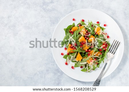 Fresh green organic salad with raw ingredients close up. Tasty salad with arugula, orange slices, pomegranate and cheese on white plate, top view. Healthy eating, dieting concept #1568208529