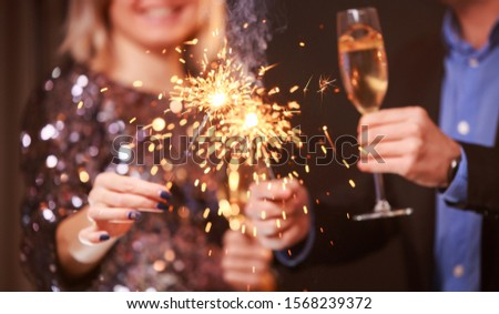 Image of couple with champagne glasses and sparklers on black background #1568239372