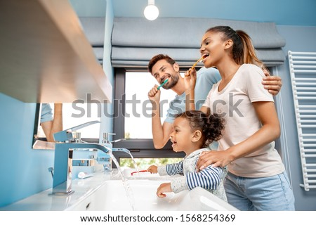 Concept of mixed race family. Low angle view of cheerful young adult man hugging happy woman and brushing teeth at morning. Father and mother standing together with african daughter in bathroom Royalty-Free Stock Photo #1568254369