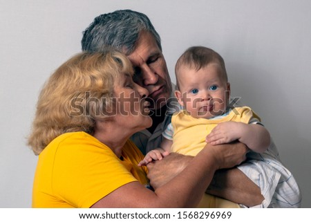 Grandfather, grandmother and baby. An old man holding his grandson in his arms #1568296969