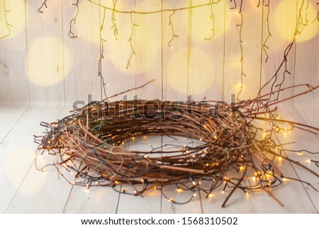 Digital backdrop, background for newborn baby boy or girl. Christmas nest,  wreath with lights, garlands on light wood background. For one year old photoshoot. Wicker nest.