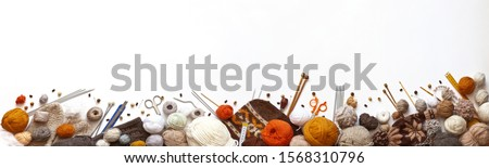 Panoramic view of composition with knitting accessories: balls of wool yarn, set of knitting needles, hooks, and other knit tools on white background. Long banner, top view, copy space, flat lay #1568310796