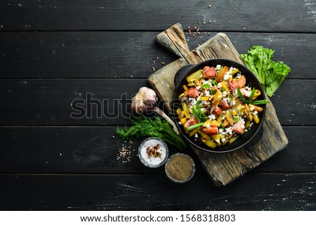 Fried potatoes with bacon and mushrooms in a pan. Top view. Free space for your text. #1568318803