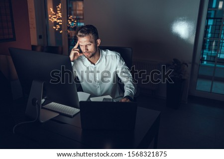 Serious male worker sitting at his workplace late at night Royalty-Free Stock Photo #1568321875