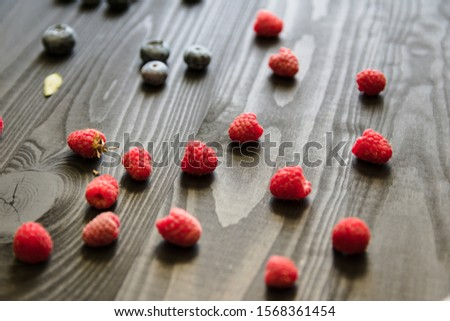 Fresh raspberries and blueberries in a mess lie on an ebony table. Healthy diet and detox concept. Berry texture #1568361454