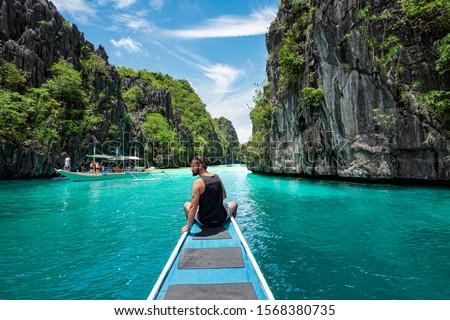 El Nido, Palawan, Philippines, traveler sitting on boat deck exploring the natural sights around El Nido on a sunny day. #1568380735