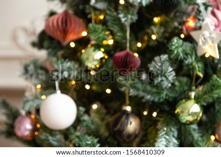 Blured photo of shiny toys and garland hanging on fir branches