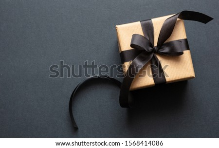 Black Friday sale concept. Gift box with black ribbon isolated against black background, top view #1568414086