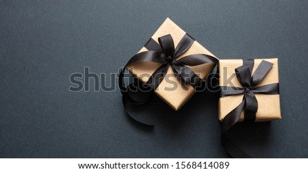 Black Friday sale concept. Gift boxes with black ribbon isolated against black background, top view #1568414089