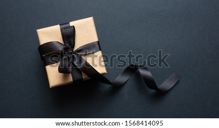 Black Friday sale concept. Gift box with black ribbon isolated against black background, top view #1568414095