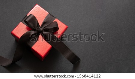 Black Friday sale concept. Red color gift box with black ribbon isolated against black background, top view #1568414122