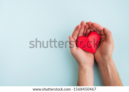 Cardiology and medical concept. Man hands hold red heart on a light blue background. Top view, copy space #1568450467