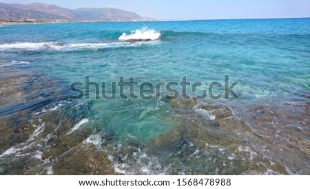 Blue clear sea water with white waves, rocks, coast and empty beach in September on the Crete Island in Greece with beautiful blue sky  #1568478988