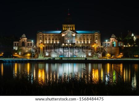 Szczecin. Night view from across the river to the illuminated historic center. Odra river. Chrobry embankments in Szczecin Royalty-Free Stock Photo #1568484475