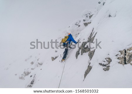 An alpinist climbing an alpine ridge in winter extreme conditions. Adventure ascent of alpine peak in snow and on rocks. Climber ascent to the summit. Winter ice and snow climbing in mountains. #1568501032