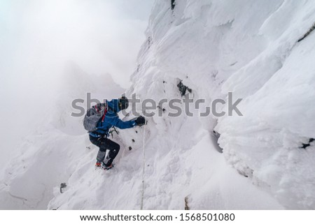 An alpinist climbing an alpine ridge in winter extreme conditions. Adventure ascent of alpine peak in snow and on rocks. Climber ascent to the summit. Winter ice and snow climbing in mountains. #1568501080