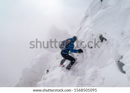 An alpinist climbing an alpine ridge in winter extreme conditions. Adventure ascent of alpine peak in snow and on rocks. Climber ascent to the summit. Winter ice and snow climbing in mountains. #1568501095