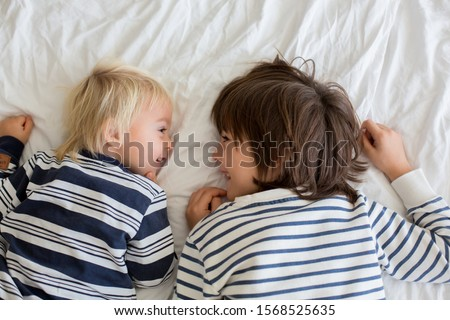 Children, brothers, playing at home, tickling feet laughing and smiling #1568525635