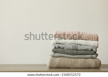 a stack of warm sweaters on the table on a colored background.