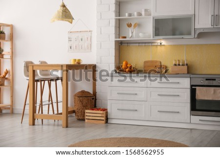 Modern kitchen interior with stylish wooden table #1568562955